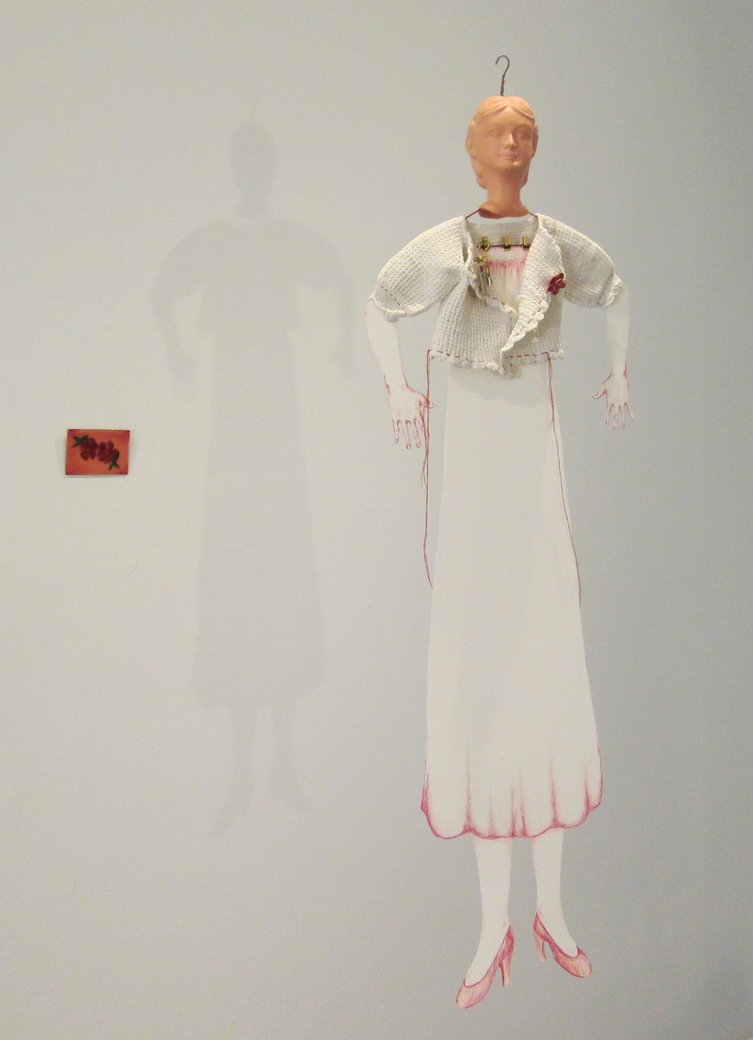 "Paper Doll; Cast rubber, old doll clothes and hanger, paper, coloured pencil, costume jewelry; 37""h x 12""w x 3""d; 2015"